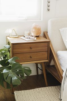 almost makes perfect bedroom - bed. Bedside table. Salt lamp. Plant. Neutrals, wood and greenery.