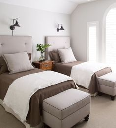 guest bedroom with twin beds, upholstered headboards and ottomans