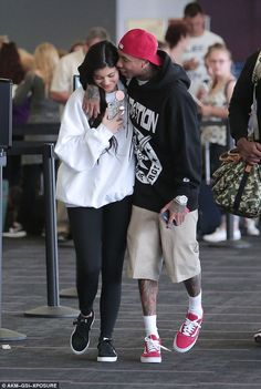 Kisses for Kylie Jenner! Tyga plays the doting boyfriend as he gets hands on with his ex when they touch down at Los Angeles airport on Friday