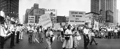 Marchers in the Labor Day Parade walk through Campus Martius carrying signs that denounce war and promote disarmament, Detroit, Michigan.