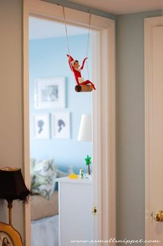 Swinging from the doorframe on a toilet-paper roll