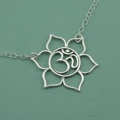 I love this so much.  Genius birthday gift. Hint hint   Om Lotus Necklace - sterling silver om pendant - yoga jewelry - lotus flower jewelry - christmas gift idea on Etsy, $46.00