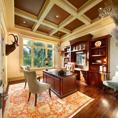 Pleasing to the eye, this home office could cater to both genders. Taxidermy and mahogany bookshelves lends a more masculine vibe, while details like the traditional rug and tufted chairs offer a bit of femininity. We especially love the coffered ceiling!