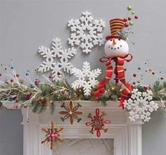 Multicolored branches, large snowflakes and Snowman Head Tree Topper on top of a candlestick, some of these items can be found in the Snowdoodles Collection by regianecasarin