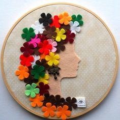 Cara de muñeca y pelo de flores en fieltro sobre bastidor