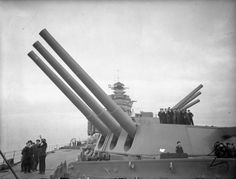 Officers and men aboard HMS Rodney observing a naval aviation parade, Sep 1940; note Rodney's primary guns at maximum elevation