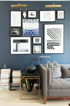 Gallery wall in living space on teal walls above gray sofa with patterned pillows