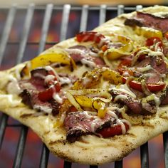 Grilled pizza with a topping of grilled steak, peppers and onions will please the meat lovers in the crowd.