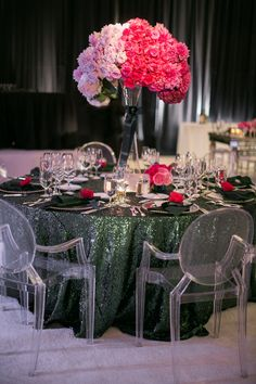 Guests were seated at round tables covered with dark green sequined linens surrounded by Ghost chairs. Towering centerpieces featured arrangements of ombré florals that transitioned from cream to dark pink. #centerpiece #sequinlinen #ghostchairs Photography: Troy Grover Photographers. Read More: http://www.insideweddings.com/weddings/jet-setter-couples-modern-wedding-with-travel-inspired-elements/528/