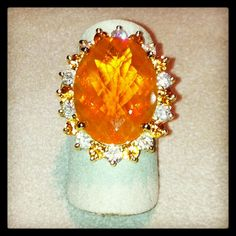 12.2ct Oval fire opal ring with orange sapphires (1.29ctw) and white diamonds (.97ctw) in surrounding halo - 14k yellow gold.  At DVVS Fine Jewelry