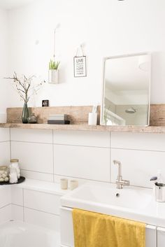 The large tiles with the wood shelf—so lovely! A tiny standing mirror becomes unexpectedly charming.