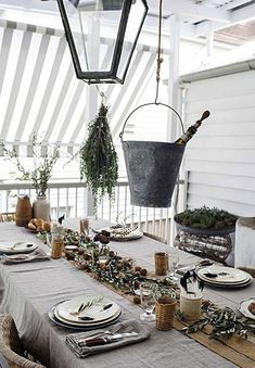 Australian designer Kara Rosenlund hung a bunch of rosemary from the pendant light over her dining table and dressed the table with clippings of olive. For more, see House Call: In the Kitchen and Beyond with Kara Rosenlund.