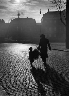 Photo by Henk Hilterman - Silhouette of father and son in the dark with newly purchased Christmas tree walking down the street. Haarlem, the Netherlands 1949.
