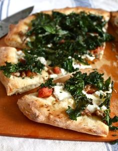 Sausage Pizza, Topped with Crispy Kale makes one large (12- to 14-inch) pizza 1 14.5-ounce can diced tomatoes with Italian seasoning 5 large curly kale leaves (or a small bunch of lacinato kale) 1 to 2 tablespoons olive oil 1/3 pound sweet Italian sausage 1 store-bought pizza dough, at room temperature 1/2 pound fresh mozzarella, cut into thin slices