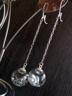 BOUCLES EIAO CHAINETTE Les boucles bulles EI AO signifient naissance du monde, de la lumière en tahitien. Elles vous offrent un bout de rêve…  - Keishis de Tahiti  - Bulle de verre: 16 mm  - Dimension apprêt ovale en rhodium: 19x45 mm  - Apprêt et chaînette en argent rhodié   Bijou made in Tahiti. Livré avec une boîte nacrée explicative du concept de bulle EI AO. A l'occasion de voyages en avion, le bijou doit vous accompagner en cabine.