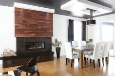 Entre la salle à manger et le séjour, un foyer à gaz réchauffe l'atmosphère. On a déposé le foyer sur une tablette identique  à celle de l'entrée et recouvert son manteau du même parement de bois. Ce rappel crée une belle unité entre les pièces.