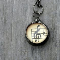 1940's vintage sheet music encased in glass. Two sided with bass clef on one side and treble clef on the other. Small sweet necklace perfect gift for musician music teacher or lover of music. See my profile for link to my shop for more details.  #musicnote #musicjewelry #music #musicnecklace #bassclef #trebleclef #giftformusician #musicteachergift #musiciangift #sheetmusic #vintagesheetmusic #artisanjewelry #jewelry #necklace #pendant #musical #clefnote #notes #bflat #necklaces…