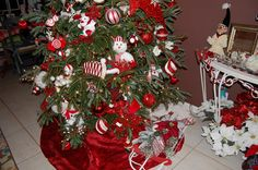 Christmas sled under tree red and white theme decor and ornaments. Lots of stuffed plush toys in tree.