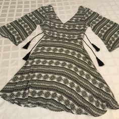 """Black & white print dress w/ 2 tie tassels Small Black and white print dress w. Flare skirt and sleeves , open back w/ 2 tassel ties and back mid zipper, fully lined   NWOT Slight high to low hem.  100% rayon. Bust 17"""" waist 12"""" (fabric has stretch) length 34"""". Can wear alone or w/ a camisole. ❤️ Anna Grace  Dresses Midi"""