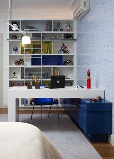 O gaveteiro serve como suporte. Ao fundo, os nichos guardam peças decorativas e livros. A luminária suspensa economiza espaço na mesa.   Foto: Sabrina Baukelmann Matar Arquitetura