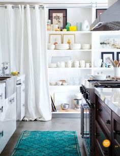 Wall of open kitchen shelving; can be concealed using canvas drapery panels    House Lust: Lakeside Bungalow | Halcyon Style