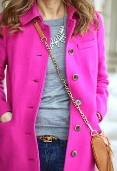 hot pink coat. dark denim pants. statement necklace. camel purse. grey top.