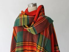 1960s vintage Erika Elias plaid wool poncho cape has a rectangular shape, completely open on the sides, and draped silhouette. Shawl collar with attached scarf and front metal zip closure. Light to medium weight wool in shades of red, green, yellow and black.   LABEL Charlie's Girls Designed by Erika Elias ILGWU   SIZE SMALL MEDIUM LARGE   MEASUREMENTS Length 28 End to End 47   CONDITION // EXCELLENT No damage, stains, or flaws. Every item is carefully cleaned and packaged. Your pur...