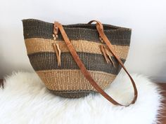 Boho Woven Market Bag w Leather Handles / Leather Straps Woven Bucket Bag Shopper / Sisal Striped Large Beach Tote / Jute Oversized Handbag  Large vintage sisal or jute tote bag with stripes and leather straps  Measurements: 17.25 wide at the top 11 tall (without straps) straps add 16 (34 long total each strap) CONDITION REFERENCE CHART RATING: Excellent color varies on the aged leather straps adding to the vintage charm of the bag. This bag has many years of life to go! Thanks for looking…