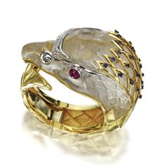 TWO-COLOR GOLD AND ROCK CRYSTAL GEM-SET 'FALCON' BANGLE Composed of a large carved rock crystal falcon head, the eyes set with cabochon rubies and round diamonds, the brow accented with a panel of round diamonds, the head feathers surmounted by a gold lattice studded with round sapphires, the body formed of a curved and hinged segment of highly textured gold resembling feathers