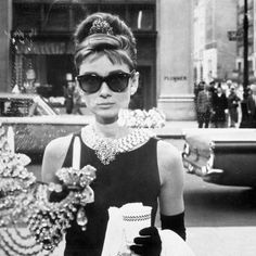"""Audrey Hepburn as Holly Golightly wearing her iconic black Givenchy dress in the 1961 movie """"Breakfast at Tiffany's"""". Audrey Hepburn Outfit, Audrey Hepburn Poster, Audrey Hepburn Mode, Audrey Hepburn Breakfast At Tiffanys, Audrey Hepburn Sunglasses, Audrey Hepburn Fashion, Audrey Hepburn Wallpaper, Audrey Hepburn Quotes, Blake Edwards"""