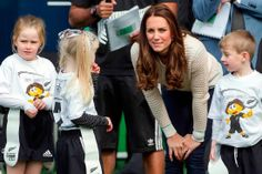 Catherine, Duchess of Cambridge, stands with young rugby players as she and her husband, Britain's Prince William.