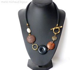 Short and bold boho necklace made with various black, off white and brown beads, various antique brass components including a beautiful toggle clasp, an original rubber cord. Includes a small transparent Micho signature charm for Marie Michaud Bijoux. Colors: black, brown, off white. All my metal components are brass. You wont risk allergies and the metal wont leave any stains on your skin. If you wish to clean your jewelry made with brass you may clean it with soapy water and a soft…
