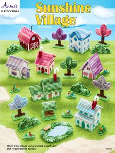 """This brightly colored village includes six tiny houses and a barn. The town isn't complete without a pond, trees, shrubs and flower gardens. Each piece is made using 7-count plastic canvas and worsted-weight yarn. Each house is between 2"""" and 4"""" tall."""
