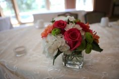 Small pink, orange, and green wedding centerpiece.  www.the-petal.com