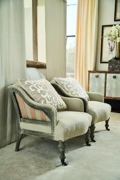 A low slipper chair, upholstered in natural herringbone linen, featuring curved arms edged with iron tacks, and turned mango wood legs on brass castors. Wingback Chair, Armchair, Neutral Bedrooms, Neutral Colour Palette, Master Bedroom, Accent Chairs, Atticus, Traditional, Slipper