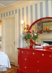 Love the blue and white striped walls with the red dresser. What a great color combo for a guest room or a boy's room!!