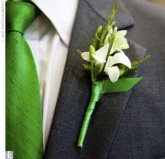 White groomsmen boutonniere wrapped with green ribbon.