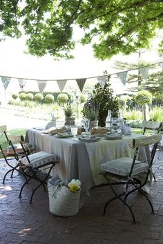 Pretty table setting, french folding chairs, and fabric bunting.  Makes me want to be there!