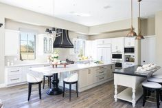 Gorgeous two tone black and white kitchen features a white French island dining table contrasted with a black wood countertop seating three backless black and white bar stools lit by Restoration Hardware Harmon Pendants.