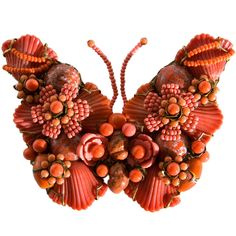pin Miriam Haskell butterfly coral hand carved brooch  USA  1930s  beads and stones are clustered to form a butterfly.