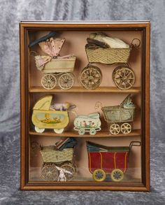 Collection of small tin doll carriages in various styles, in glass-fronted presentation. $400/700