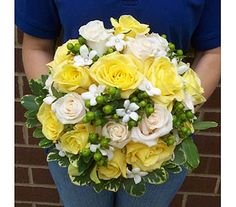 Hand tied bouquet of Vendella and Skyline roses, green hypericum berries and pearl accented stephanotis with a light collar of variegated pitta foliage.