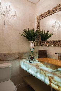 No lavabo, a designer utilizou na bancada pedra Onix acompanhada por um sistema de iluminação. A cuba, em resina dourada, possui linhas retas que contrastam com o espelho com moldura entalhada e uma arandela – ambos clássicos – na parede de frente com a porta.