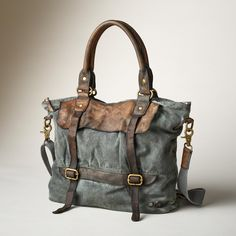 """PASSAGEWAY BAG--A canvas and leather bag with a well-traveled, timeworn appeal. Plenty of pockets inside and out with removable, adjustable strap. Each is unique. Imported. Approx. 16""""W x 5""""D x 13""""H."""