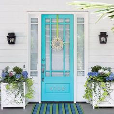 Perfect front door color turquoise, beautiful white square planter boxes and side by side door lanterns. Nice striped blue green white mat in front of the door - Love this and the subtle small wreath... symmetry cute. very coastal/ hamptons