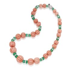 18 KARAT WHITE GOLD, CORAL, EMERALD AND DIAMOND NECKLACE, PIRANESI Of graduated design, composed of 25 fluted coral beads measuring approximately 21.7 mm to 11.2 mm, spaced by 26 fluted emerald beads weighing approximately 83.00 carats, the rondelles and clasp set with round and baguette diamonds weighing approximately 8.00 carats, length 21½ inches, with maker's mark.