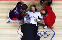 Egypt's Khalil K Abir Abdelrahman is assisted after a failed attempt during the women's 75Kg group A weightlifting competition.