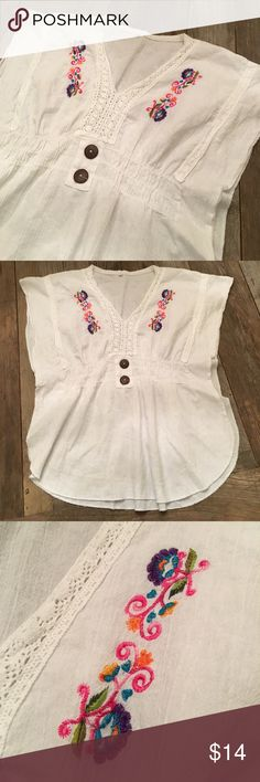 "White Embroidered Floral Summer Shirt Super cute boho summer top!  White cotton...(I'm assuming..since there is no tag except for ""M"" tag at the back of the neck) with multicolor floral embroidery and also white needlework trim and details. There are two brown buttons for pure design element on the front center, and elastic around the center of shirt..gives it a ""gathered"" feel. There is no maker tag..It doesn't look like it ever had a brand tag.  23"" shoulder to hem. 12"" chest side to side…"