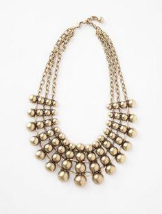 A degrade pattern of antiqued brass ball beads create a stunning collar necklace.