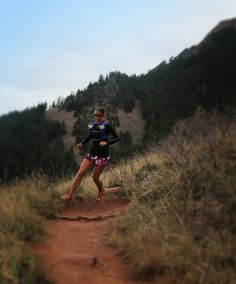 Simple Hydration Ultra Team Runner Sandi Nypaver flying down a mountain with 2 Simple Hydration Bottles tucked into a pack.